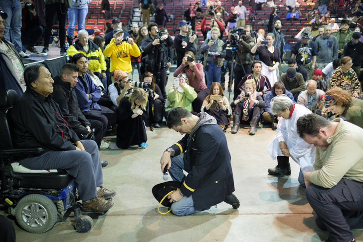 Gen. Wesley Clark Jr., middle, and other veterans kneel in front of Leonard Crow Dog during a forgiveness ceremony at the Four Prairie Knights Casino & Resort on the Standing Rock Sioux Reservation on Monday, Dec. 5, 2016.